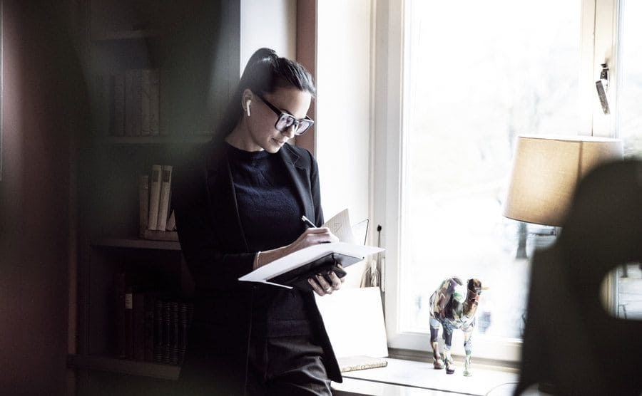 A woman wearing all black with an airpod in her ear writing in a notebook
