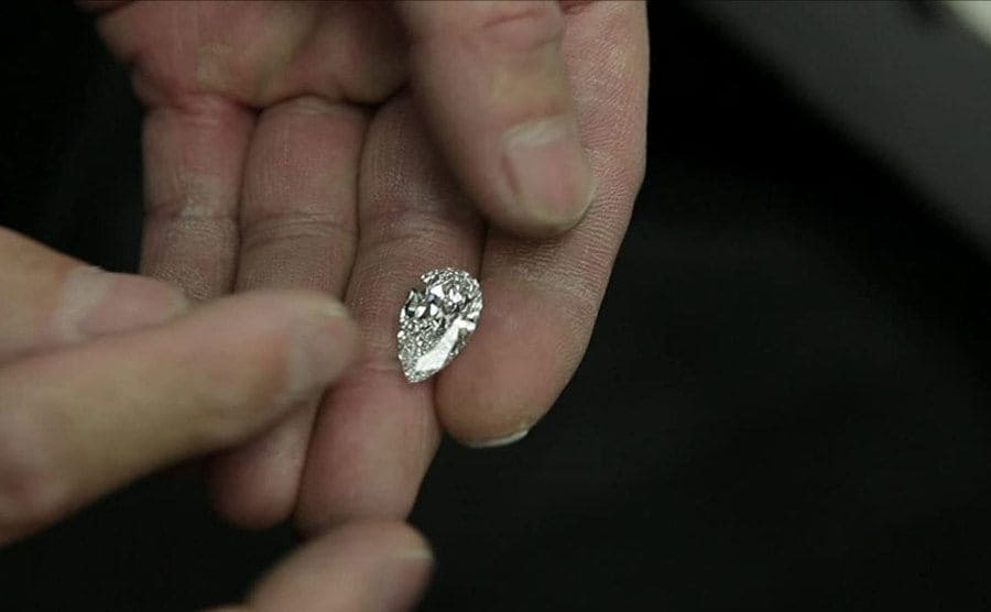 A person holding a large diamond in their hand