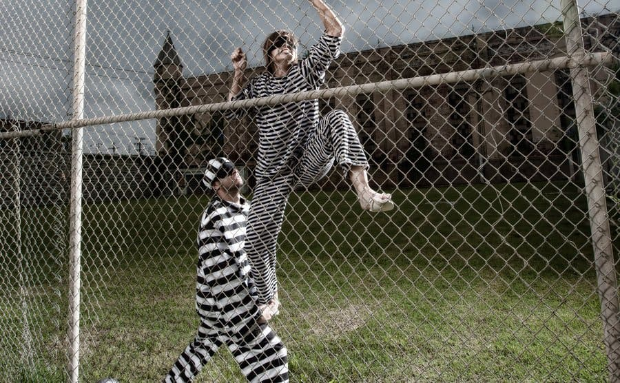 Two people in black and white striped jumpsuits helping each other break out of jail