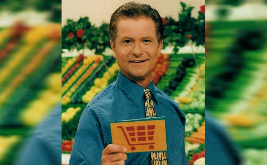 David Ruprecht holding a card with an illustration of a shopping cart on the front in the refrigerated vegetable section of the grocery store