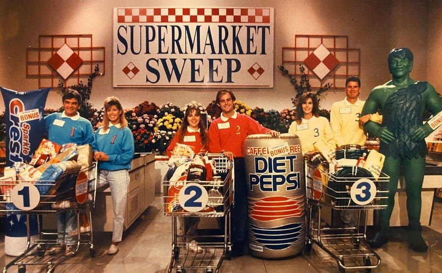 Contestants on Supermarket Sweep with their full carts and large blow-up products standing by the registers