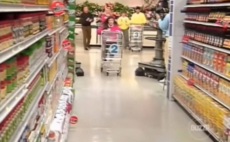 A Supermarket Sweep contestant pushing a cart through the narrow aisle.