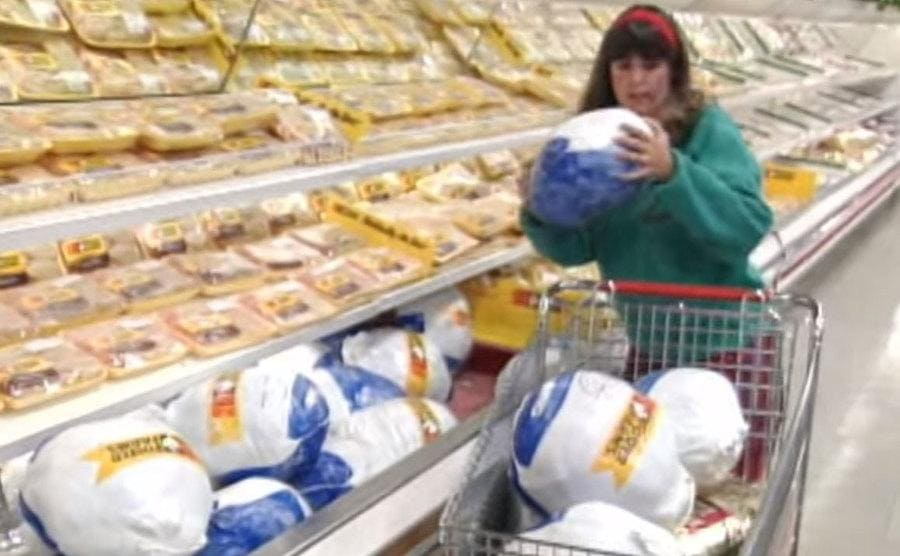 A woman competing on the show grabbing and tossing a full turkey into her cart.