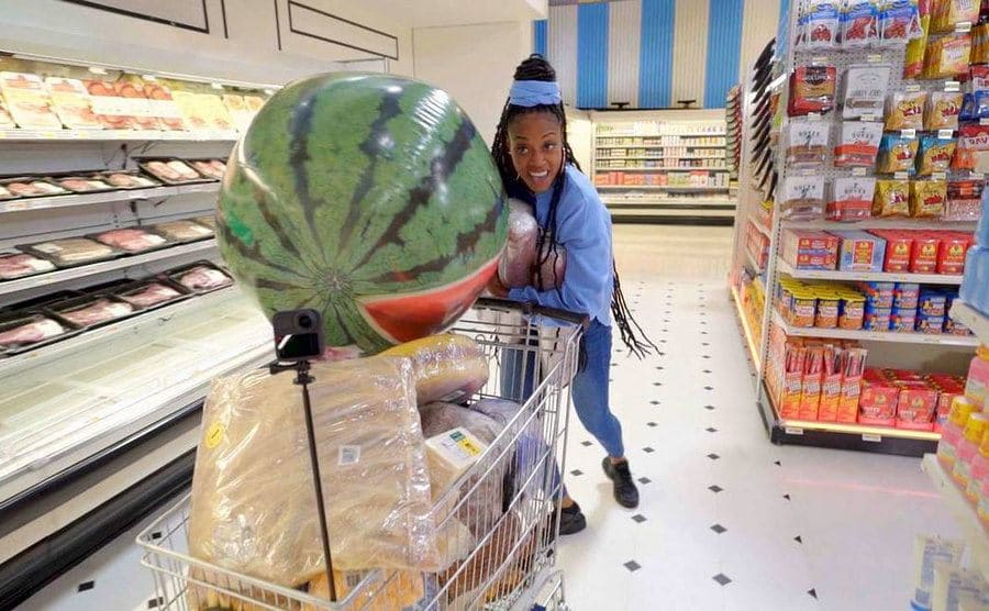 A Woman pushing a shopping cart filled with items, including a beach ball in the shape of a watermelon.