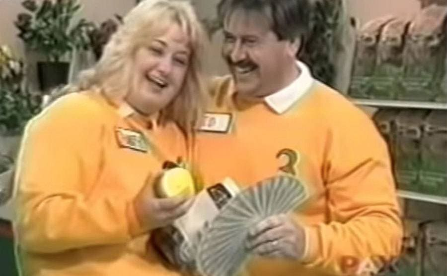 Two contestants holding their prize money in their hand, crying tears of joy.
