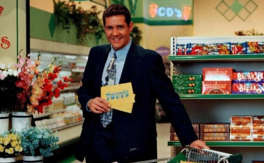 Dale Winton, the host of the British Supermarket Sweep standing over a shopping cart filled with groceries.