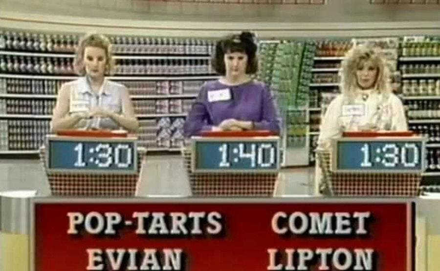 Supermarket Sweep contestants answering trivia questions with a buzzer.