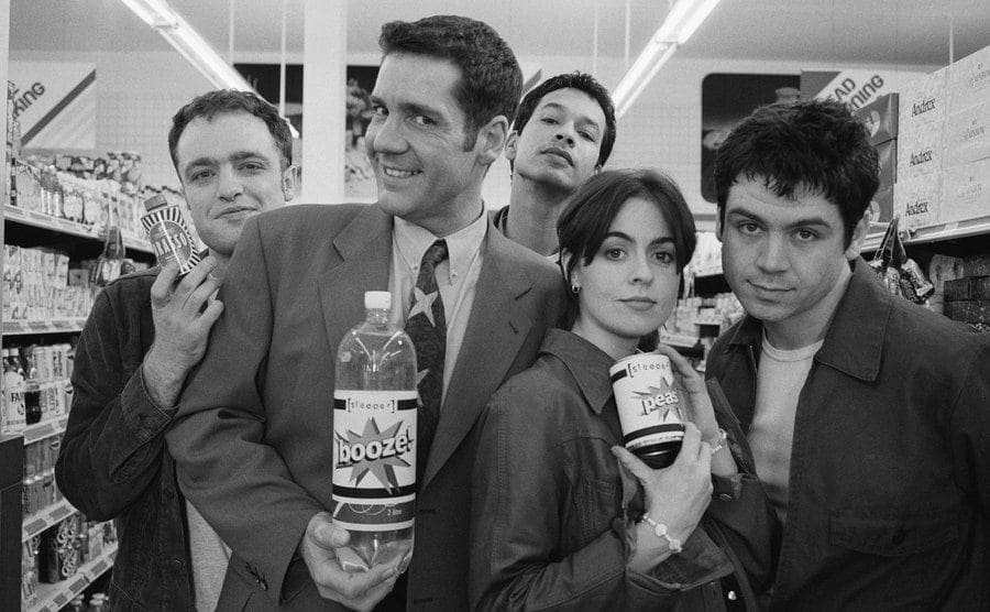 Dale Winton with the indie rock group Sleeper holding products in a supermarket aisle