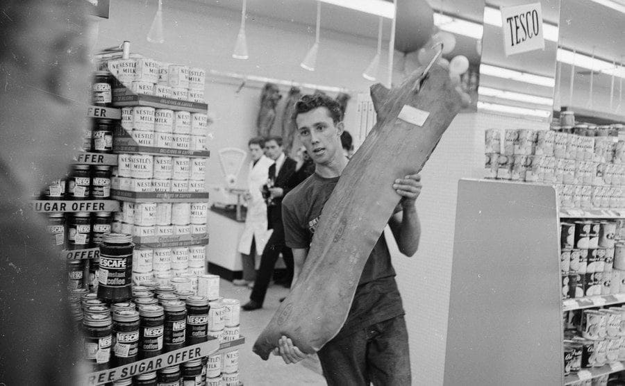 Joe Buzidragis, whose parents won a US supermarket sweep contest, helps them repeat their prize-winning feat while carrying a large piece of meat.