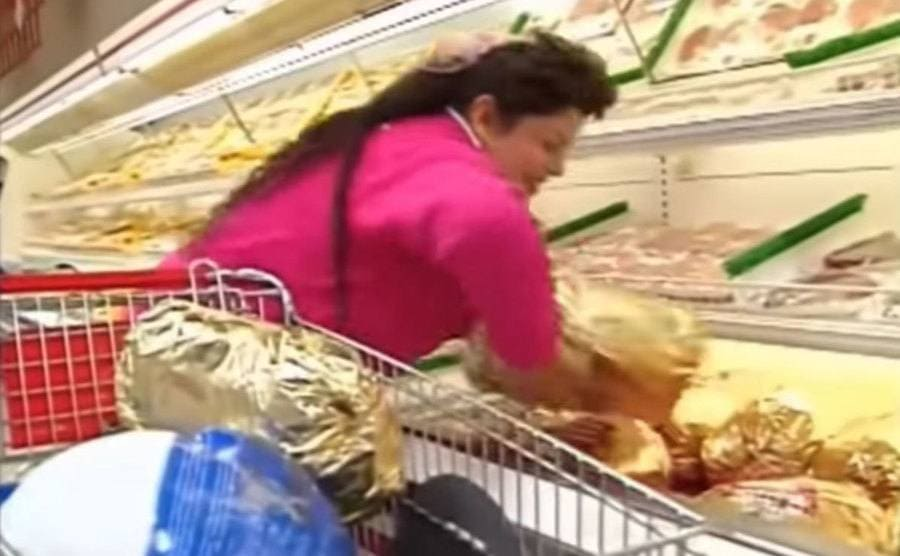 a female contestant grabs meat off the shelves and throws it into her cart.
