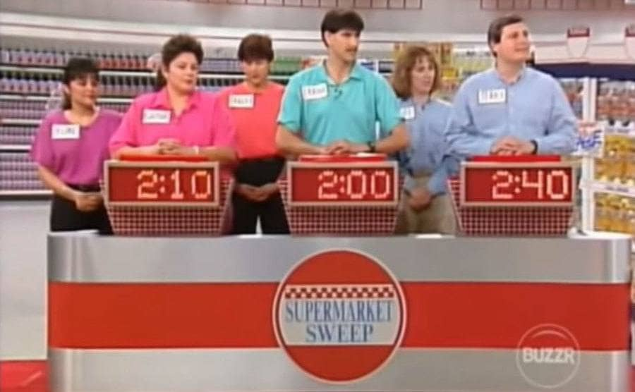 Three groups of contestants coupled up with their hands on the buzzer.