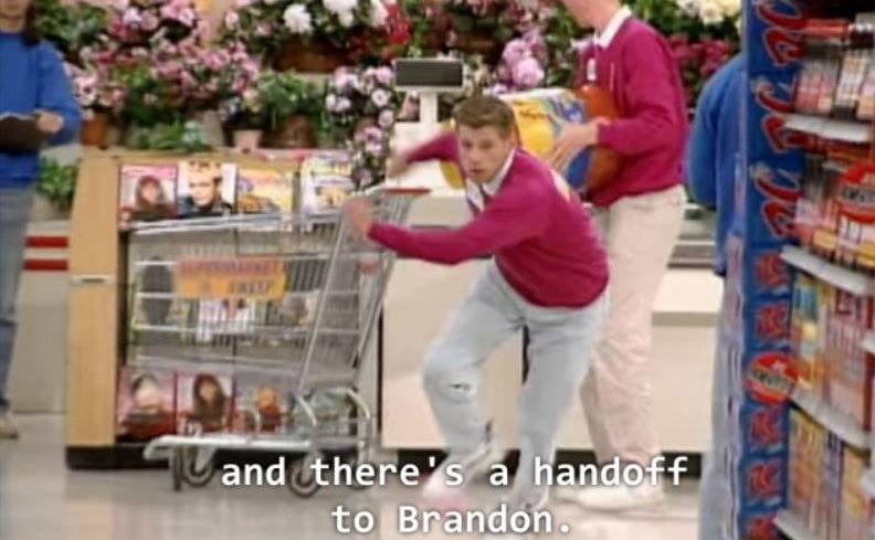 Kevin handing off a cart to Brandon while running around set to complete the task.