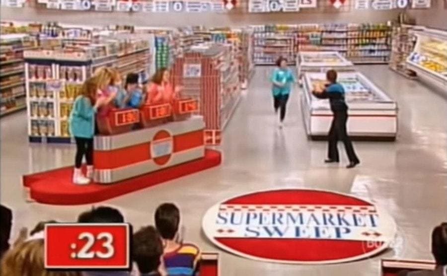 A contestant running next to the freezer section of the supermarket with '23' seconds left on the clock
