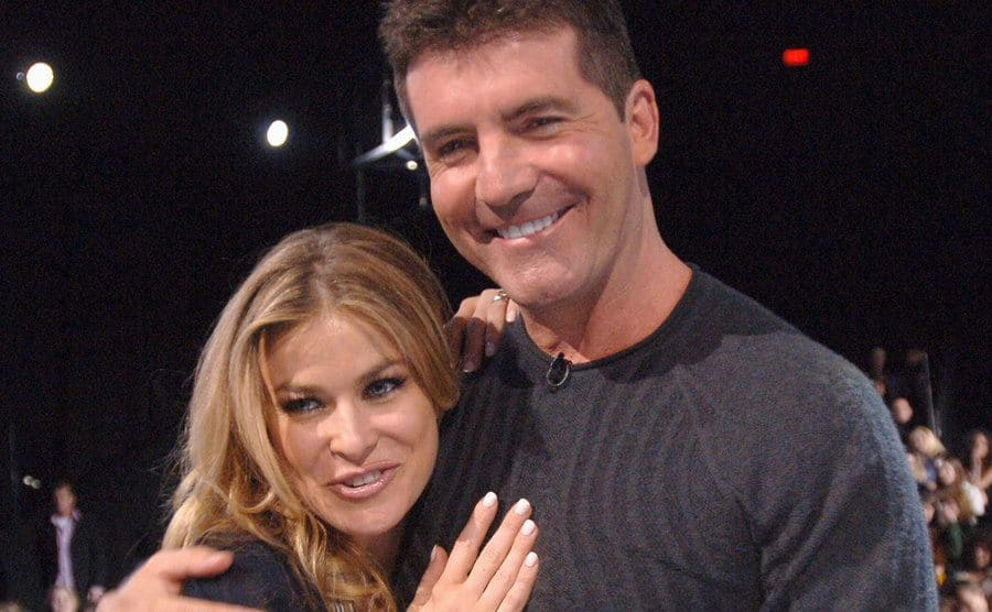 Carmen Electra and Simon Cowell posing together on the set of American Idol