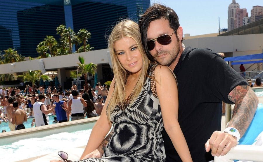 Carmen Electra and Rob Patterson posing together on a lounge chair at a pool party