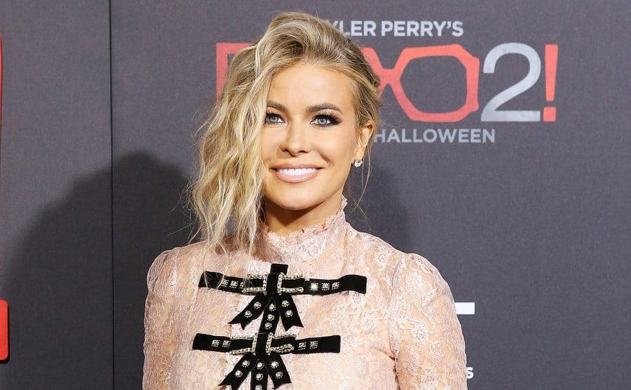 Carmen Electra on the red carpet in a peach mock turtleneck shirt with black bows
