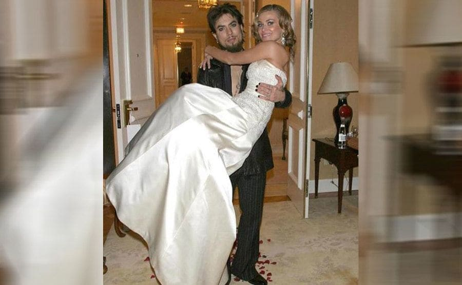 Dave holding Carmen on their wedding day with red rose petals spread around the floor