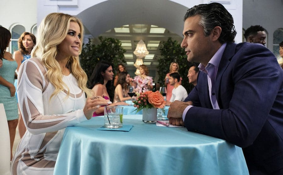Carmen Electra and Jaime Camil sitting at a table with a light blue-green tablecloth
