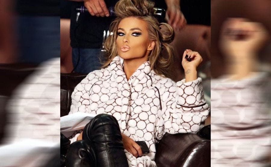Carmen Electra having her hair done wearing a fluffy white patterned robe