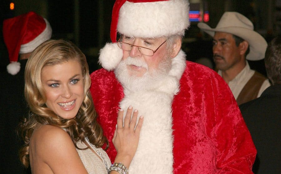 Carmen Electra posing with a man dressed as Santa Clause