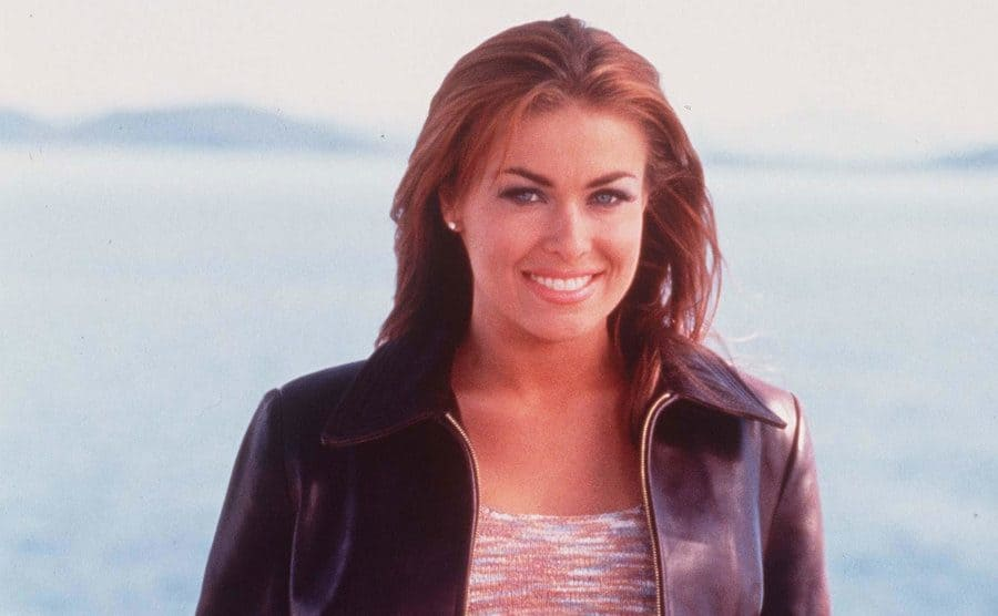 Carmen Electra posing leaning on a railing next to the ocean