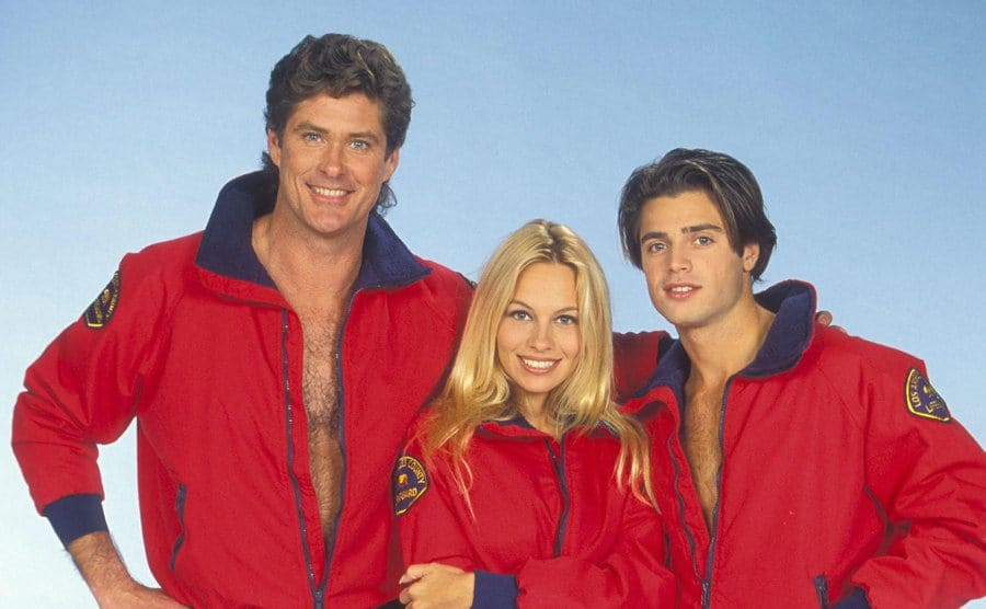 David Hasselhoff, Pamela Anderson, and David Charvet posing with their lifeguard jackets in front of a blue background