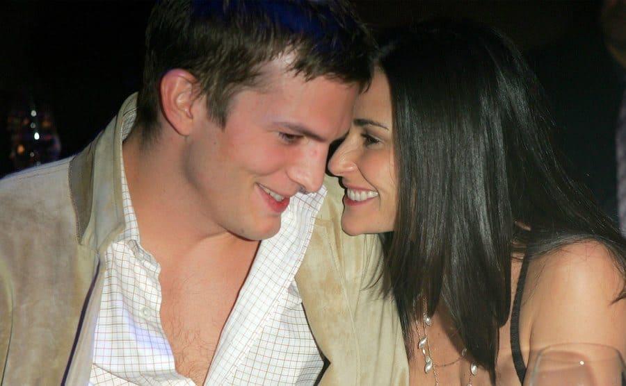 Ashton Kutcher and Demi Moore sharing an inside joke at a dinner
