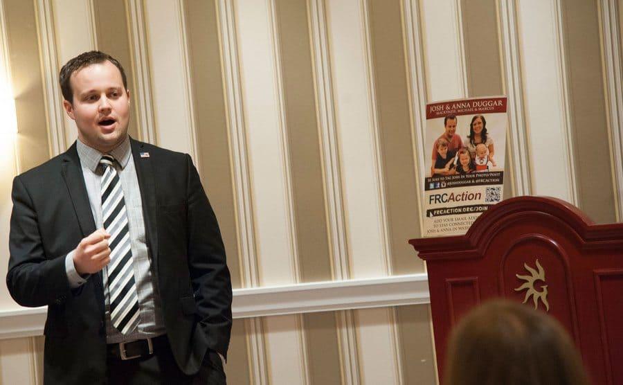 Josh Duggar speaking before a room of people in a suit and tie.