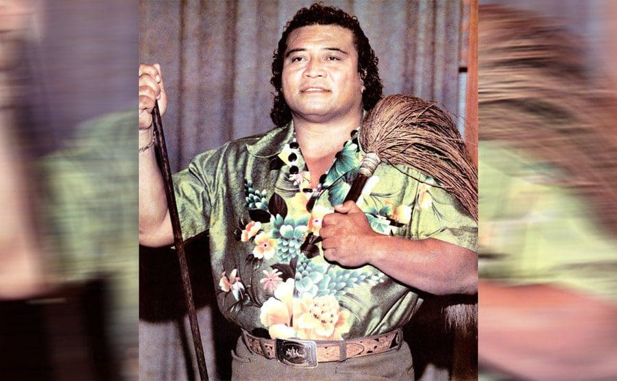 Peter Maivia posing with a broom