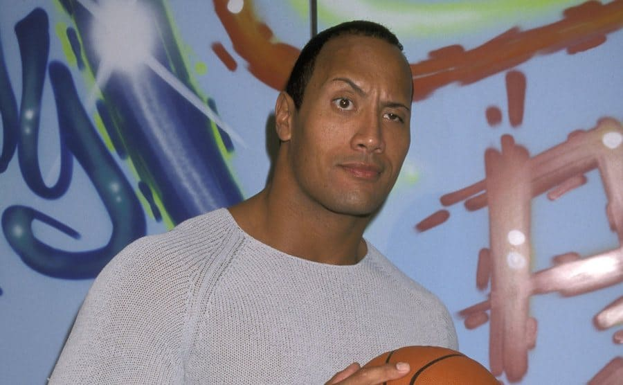 Dwayne Johnson holding a basketball on the red carpet