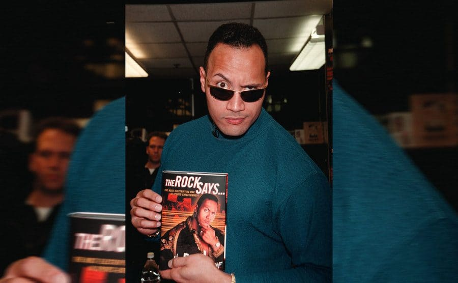 Dwayne Johnson holding up his book, which reads 'The Rock Says'