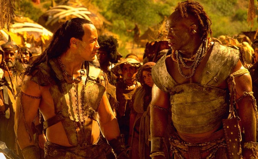 Dwayne Johnson and Michael Clarke Duncan dressed up in a scene from The Scorpion King, looking intensely.