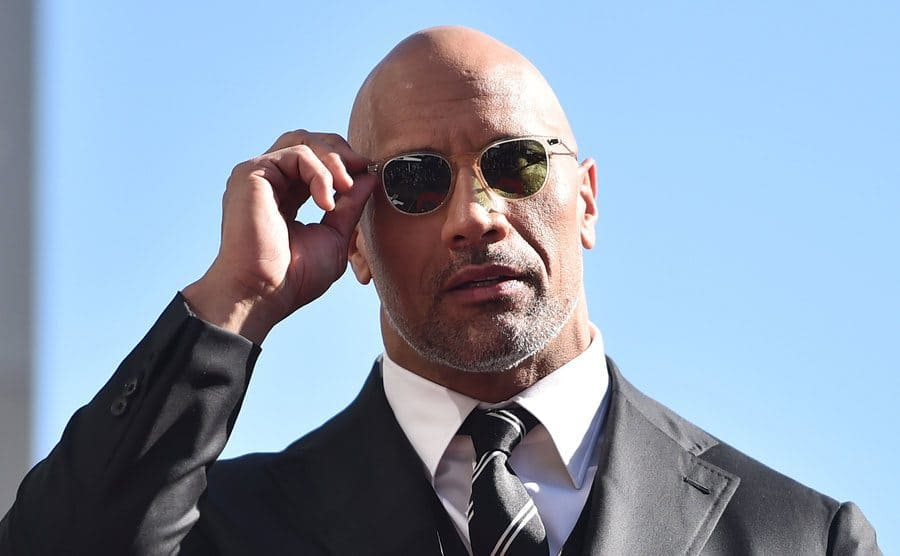 Dwayne Johnson holding onto his sunglasses walking on a sunny day