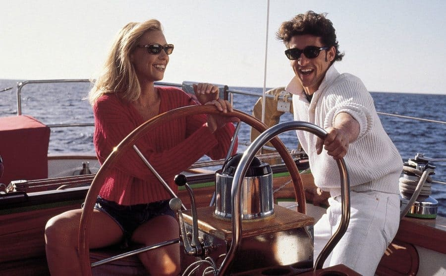 Olivia d'Abo and Patrick Dempsey behind the wheel of a yacht in a scene from Bank Robber