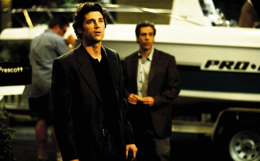 Patrick Dempsey standing in front of a man and a boat in a scene from Scream 3