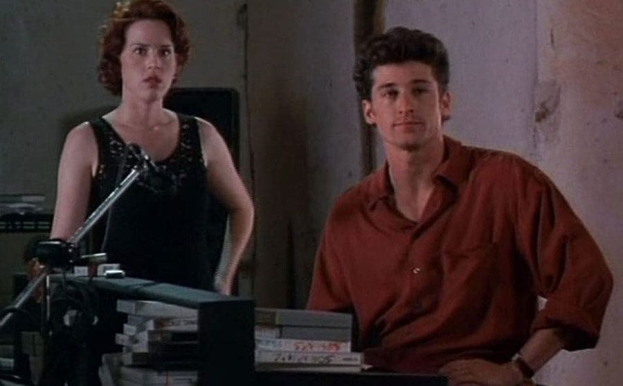 Molly Ringwald and Patrick Dempsey sitting in a make-shift recording studio
