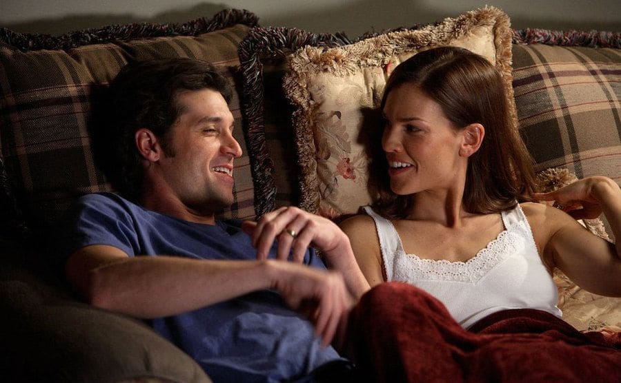 Patrick Dempsey and Hilary Swank lounging on the couch talking and laughing