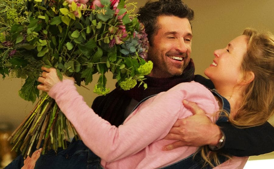 Patrick Dempsey swooping Renee Zellweger off of her feet, who is holding a large bouquet of flowers