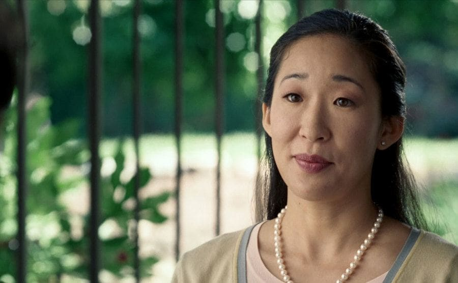 Sandra Oh dressed up in pearls at the front door of a persons home in Hard Candy