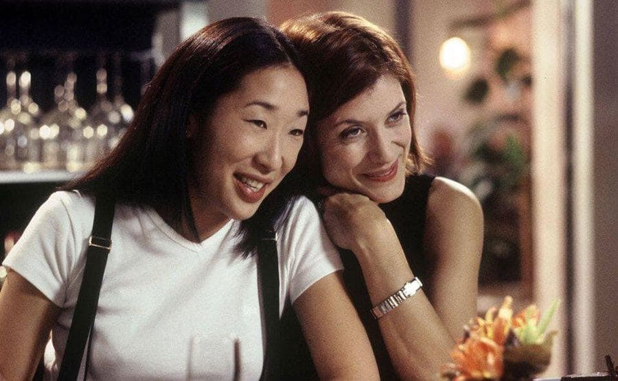 Sandra Oh and Kate Walk leaning on a bar side-by-side smiling
