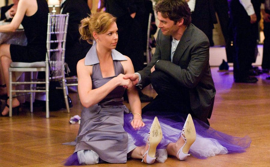 Katherine Heigls sitting on the ground in a purple bridesmaids dress with James Marsden knelling besides her taking her hand to help her up