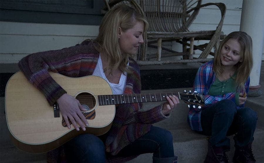 Katherine Heigl playing the guitar with her daughter in the film Jackie and Ryan sitting on wooden front porch steps