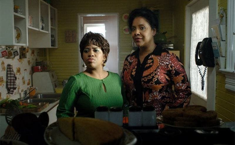 Chandra Wilson and Phylicia Rashad standing in a mustard yellow kitchen in a scene from Frankie and Alice