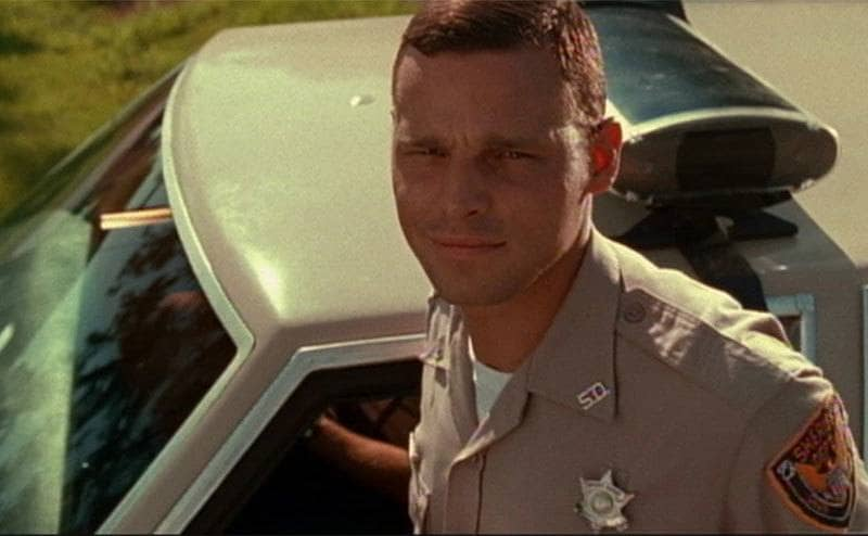 Justin Chambers as an officer standing next to his truck
