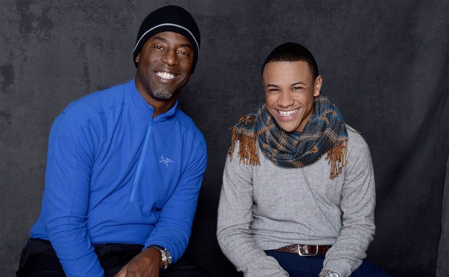 Isaiah Washington and Tequan Richmond posing for a portrait on a wooden bench on front of a grey curtain