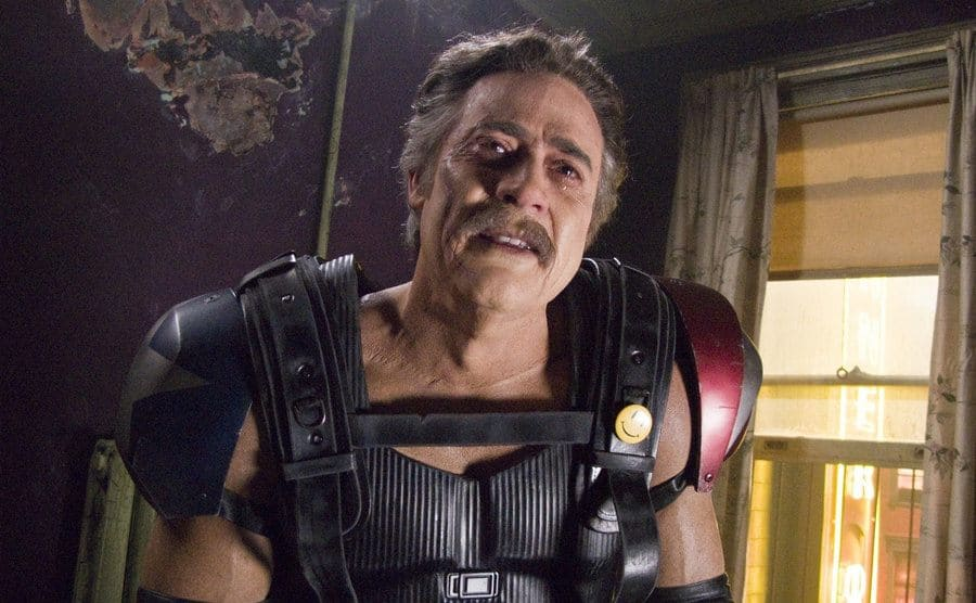 Jeffrey Dean Morgan in costume standing in an old worn-down room in a scene from Watchmen