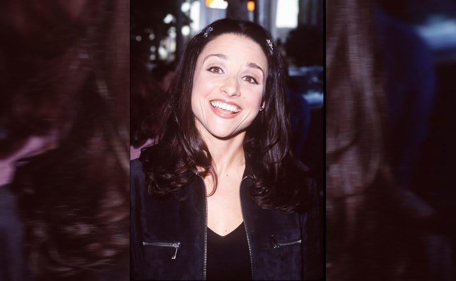 Julia Louis Dreyfus smiling while arriving at a movie premiere