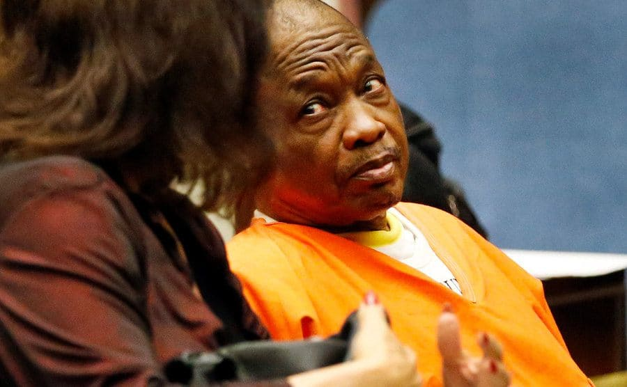 Lonnie Franklin Jr., right, the alleged Grim Sleeper serial killer accused of murdering ten women in South Los Angeles, listens to one of his attorneys in court.