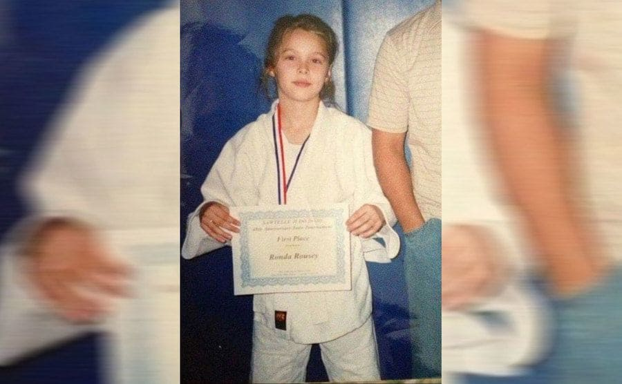 Ronda Rousey holding a certificate as a young girl with her Gi on
