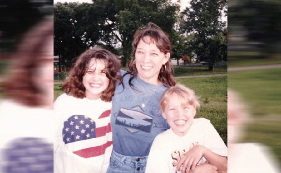 Ronda when she was younger with her sister and mother posing in a park